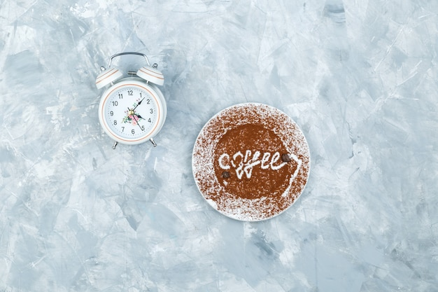 Будильник и тарелка с кофейным словом на шероховатом сером фоне