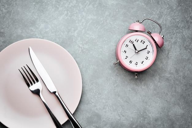 알람 시계와 칼 붙이 접시. 간헐적 단식, 점심 시간, 다이어트 및 체중 감소의 개념
