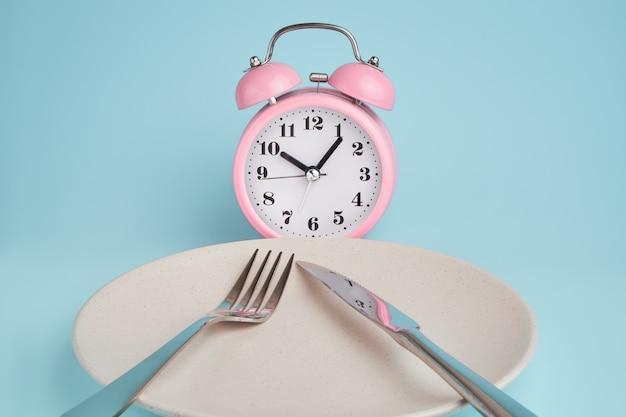 Будильник и тарелка со столовыми приборами. концепция прерывистого поста, обеда, диеты и похудения