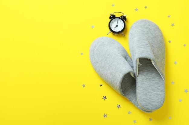 黄色の目覚まし時計とスリッパ