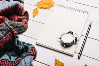 Alarm clock and stationery near scarf and autumn leaves