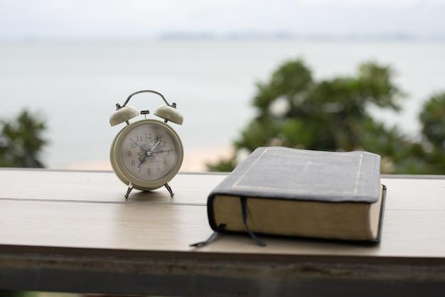 目覚まし時計と聖書研究の準備のための朝の木製テーブルの上の聖書。
