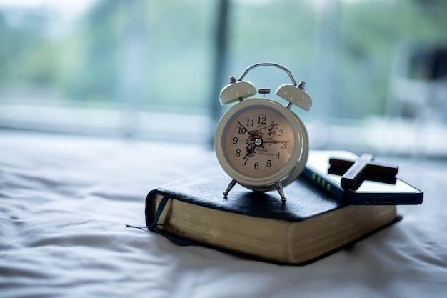 目覚まし時計とベッドの上の聖書は聖書研究の準備をします。