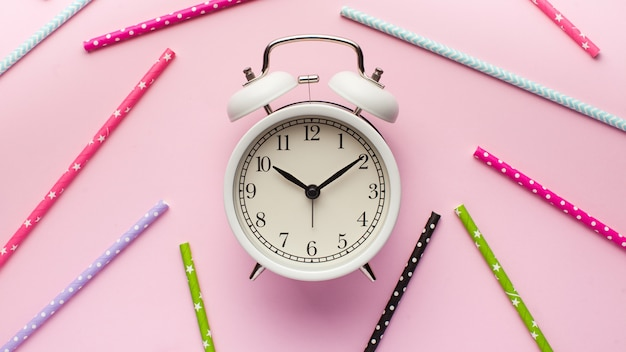 Alarm clock around multi-colored paper tubes for cocktails on a pink background.