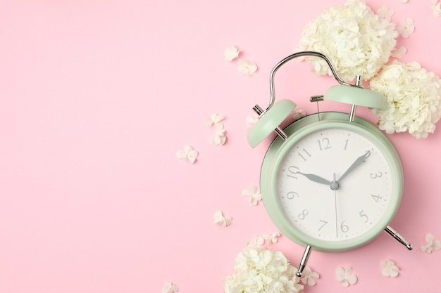 Alarm clock and beautiful hydrangea flowers on pink space
