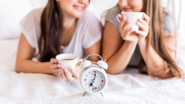 Alarm clock on the bed with two women