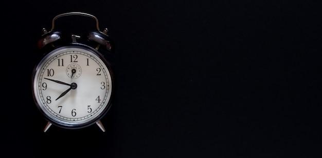 Alarm clock on a black background. minimalism. copy space.