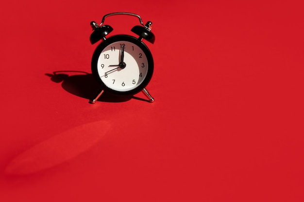 Alarm clock black on red background. close up shot. top view.