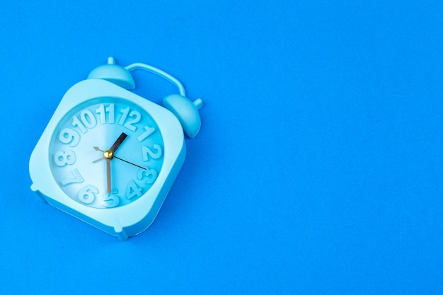 Alarm clock on blue background. pastel minimalism. copy space