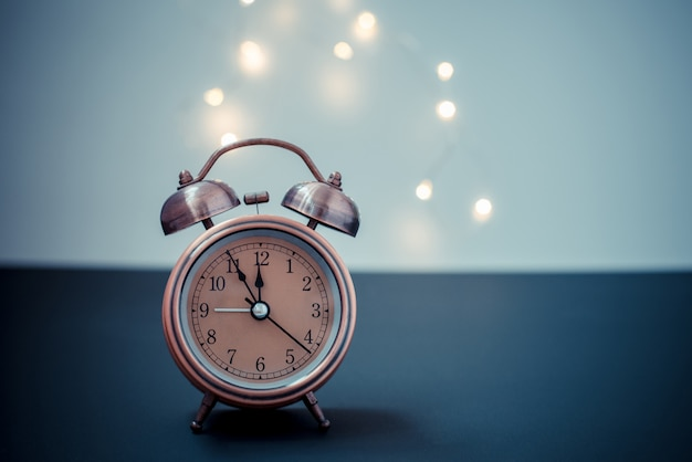 Alarm clock on blurred christmas decoration