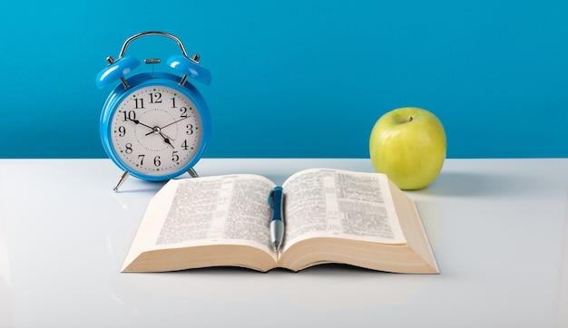 Будильник, книга, яблоко на столе.