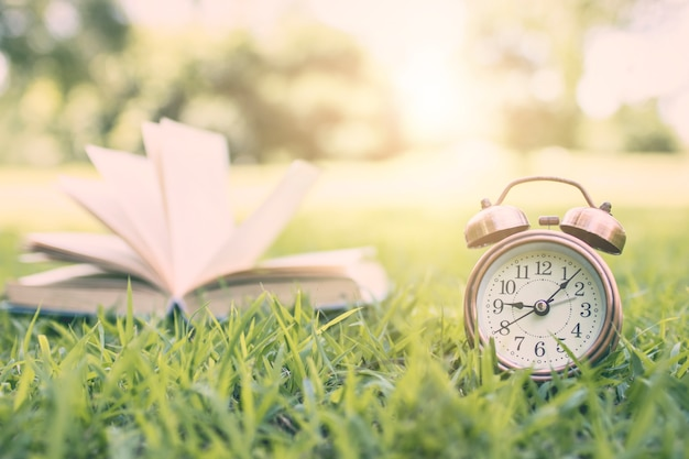 Alarm clock and book in park, time for learning and reading concept