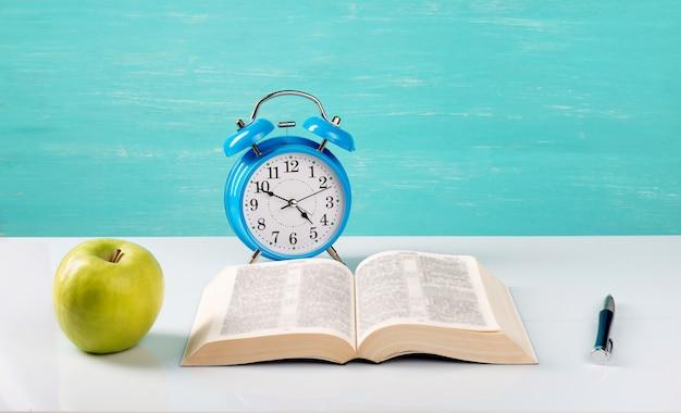 Будильник, книга, ручка, яблоко на столе.