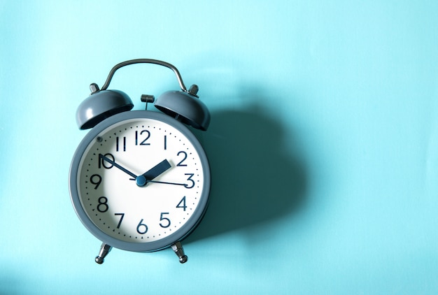 The alarm clock on bright blue background, time management concept
