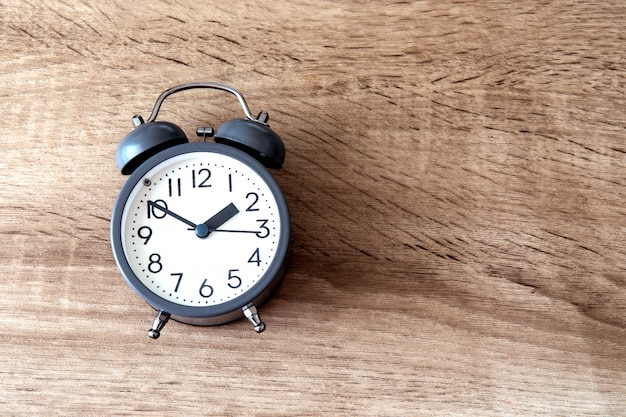 Alarm clock on brown wooden  , a time management