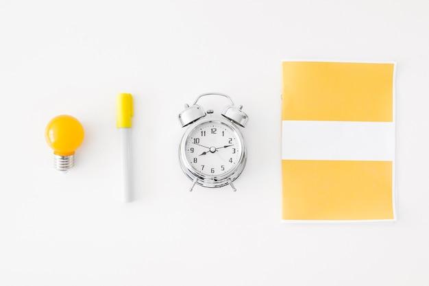 Alarm clock and bulb near stationery