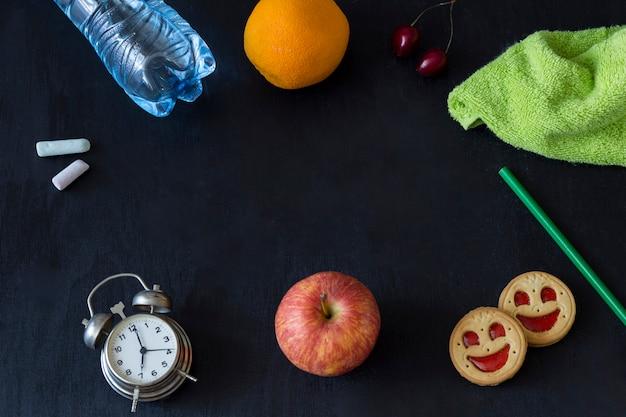 Alarm clock, chalk, apple, biscuit, pencil, cherry, orange, bottle of water