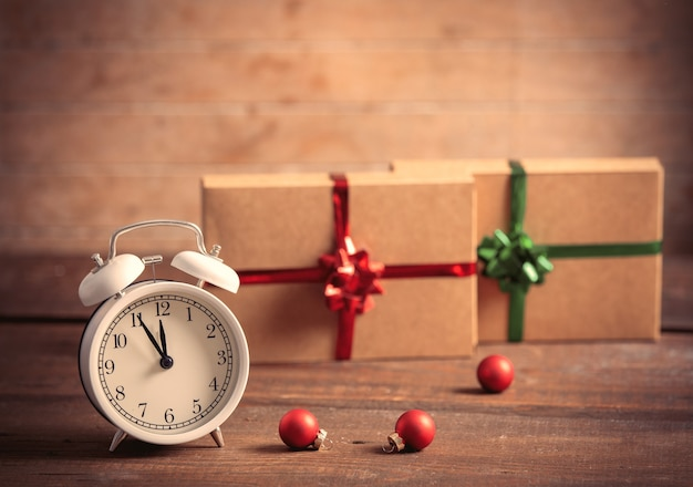 Alarm clock and christmas gifts on background