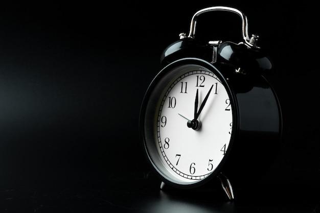 Alarm clock close up on black surface