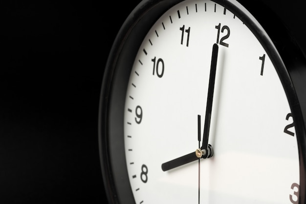 Alarm clock close up on black wall