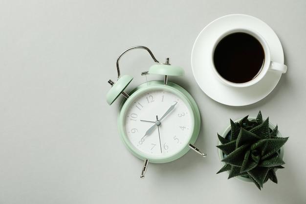 ライトグレーの背景に目覚まし時計、コーヒー、多肉植物