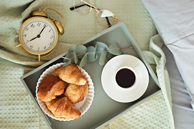 Alarm clock and coffee cup at bed in sunny room. easy morning start, positive day beginning, waking up, new day, breakfast in bed concept. flat lay, top view