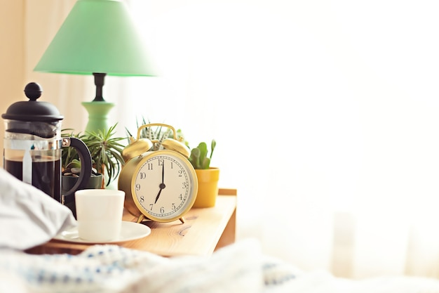 Alarm clock and coffee cup at bed in sunny room. easy morning start, positive day beginning, waking up, new day concept