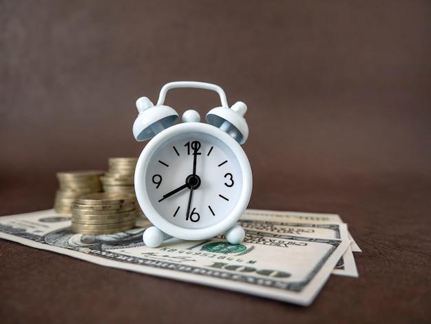 어두운 배경에 알람 시계, 동전 및 지폐. 비즈니스, 금융 개념 및 돈과 시간 절약의 아이디어.