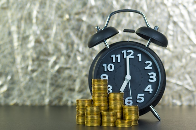 Alarm clock and coins stacks on table