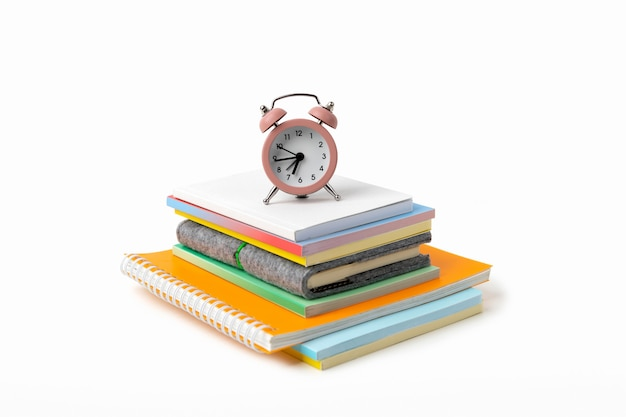 Будильник, красочные блокноты и карандаши на белом столе с копией пространства. обратно в школу, работа из дома концепции