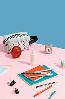 コピースペースのあるピンクのテーブルに目覚まし時計のカラフルなメモ帳ペンと手指消毒剤