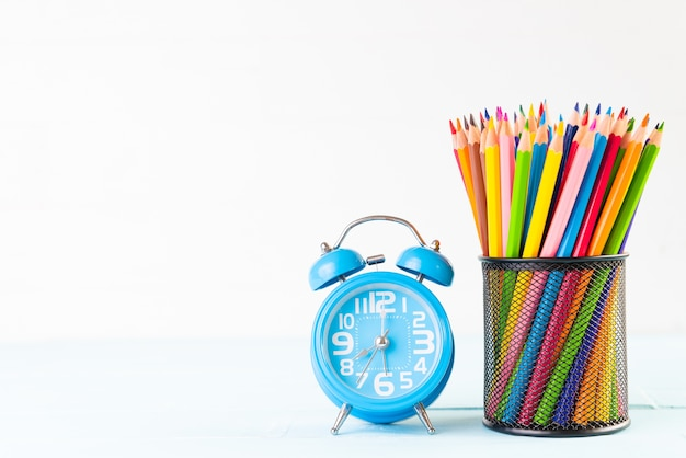 Alarm clock and colorful pencils on white wooden background.