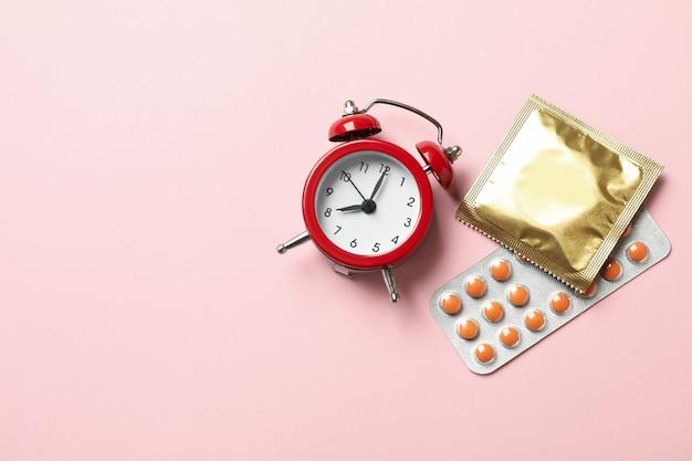 알람 시계, 콘돔 및 분홍색 배경에 알약