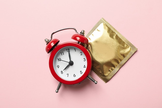 Alarm clock and condom on pink surface