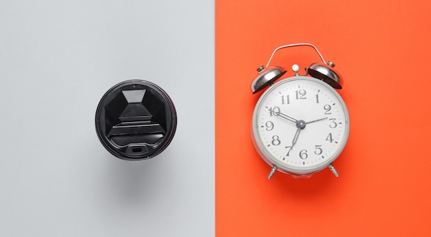 Alarm clock, container with coffee on orange gray table. top view