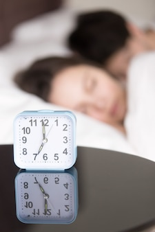Alarm clock and couple asleep early in the morning, vertical