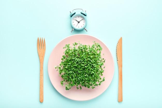 알람 시계, 칼 붙이 및 녹지가 있는 분홍색 접시. 간헐적 단식, 점심 및 다이어트 개념.