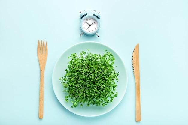 알람 시계, 칼 붙이 및 녹지가 있는 접시. 간헐적 단식, 점심 및 다이어트 개념.