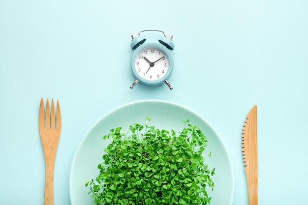 Будильник, столовые приборы и тарелка с зеленью на синем.