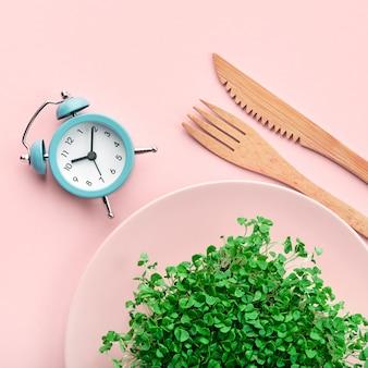 Будильник, столовые приборы и тарелка с зеленью на розовом. прерывистое голодание и концепция диеты.
