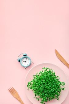 알람 시계, 칼 붙이 및 분홍색에 녹지가 있는 접시. 간헐적 단식, 점심 및 다이어트 개념.