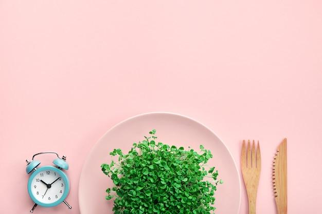 Будильник, столовые приборы и тарелка с зеленью на розовом.
