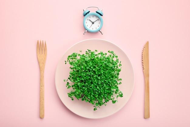 Будильник, столовые приборы и тарелка с зеленью.
