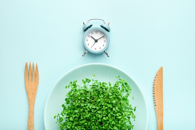 Alarm clock, cutlery and plate with greenery on blue.