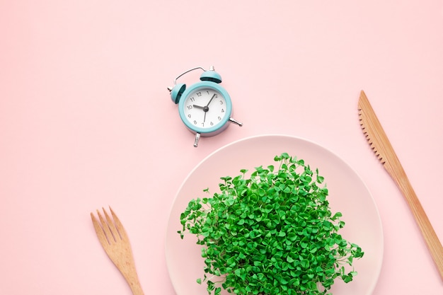 Alarm clock, cutlery and plate with greenery on pink