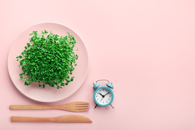 Alarm clock and cutlery with plate with greenery