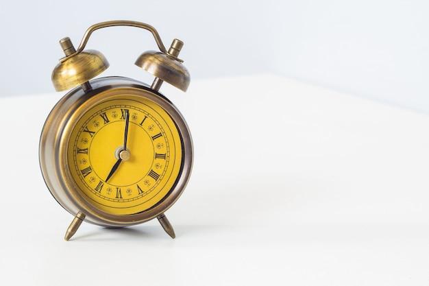 Alarm clock at eight o'clock on wood table.