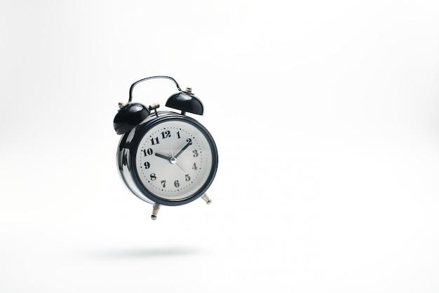 白に落ちる目覚まし時計。