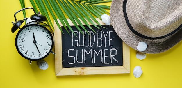 Alarm clock fedora hat, palm leaf, sea shells and blackboard room