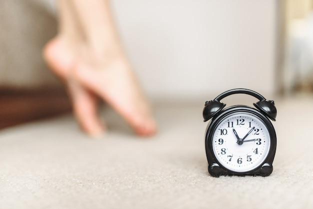 Alarm clock on the floor against female legs, waking up concept. good morning, sleeping